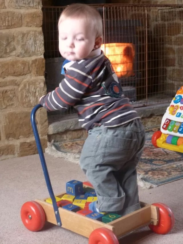 riding in his toy block trolley