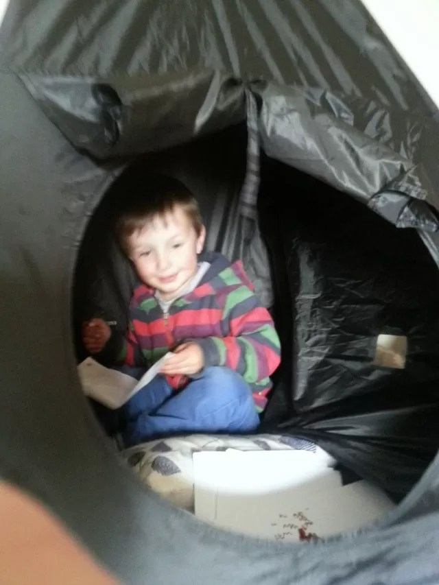 playing inside his Crayole crazy glow tent