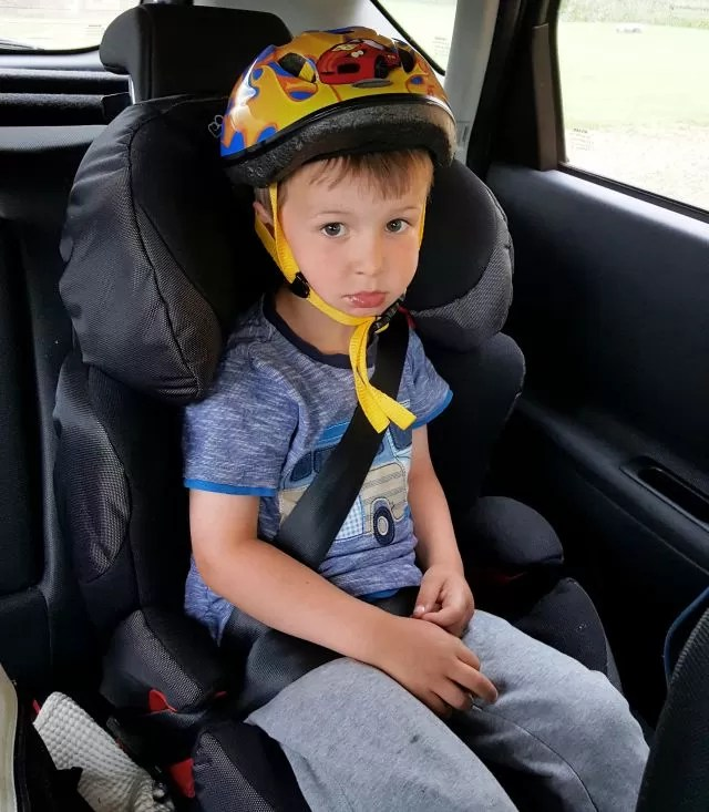 wearing a cycling helment in his car seat