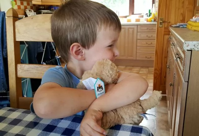 hugging his jellycat dog