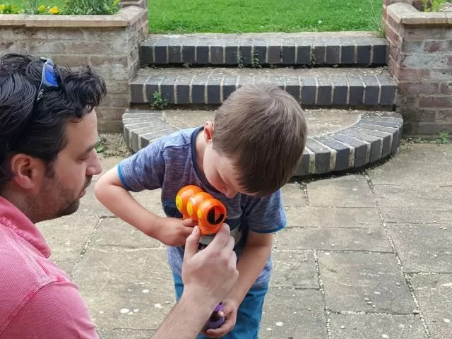 Trying to make his bubble gun work