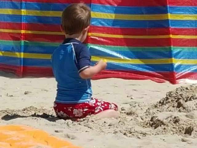 Playing in the sand by a windbreak at Weymouth beach