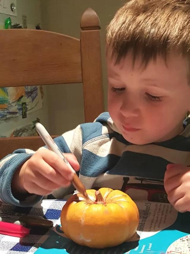 sharpie decorating the pumpkins