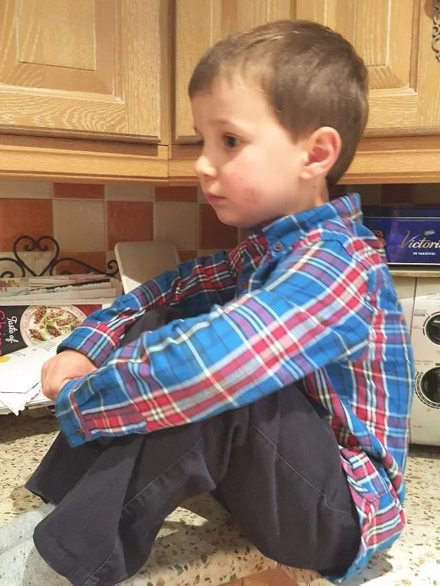 smart boy sitting on the kitchen worktop