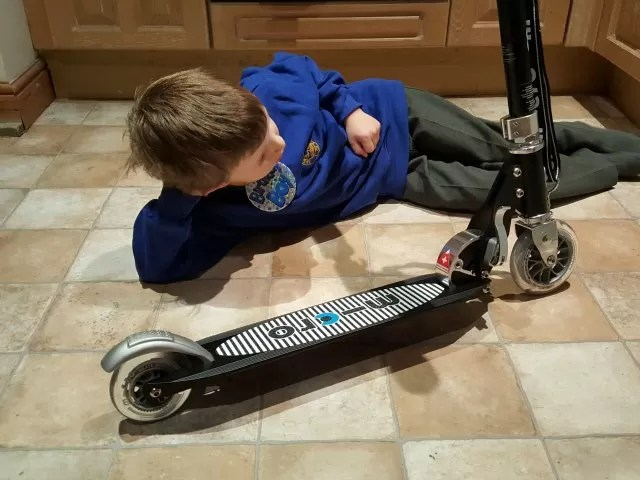 admiring his new micro scooter