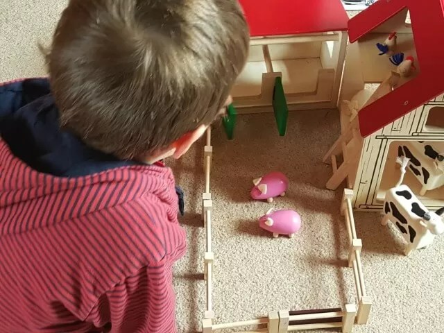 playing with a wooden farm set