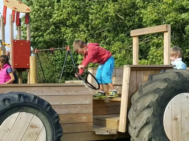 playing on a playground wooden tractor
