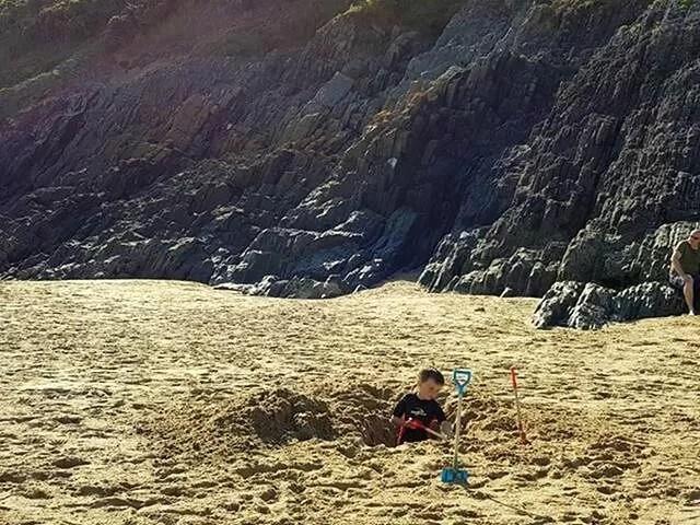 digging holes at three cliffs bay