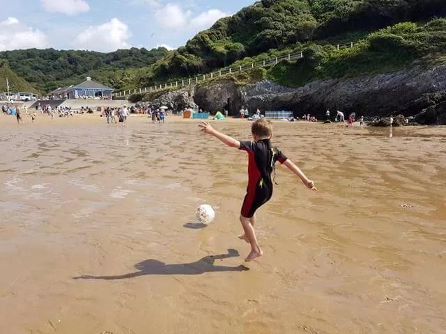 kicking football at caswell bay