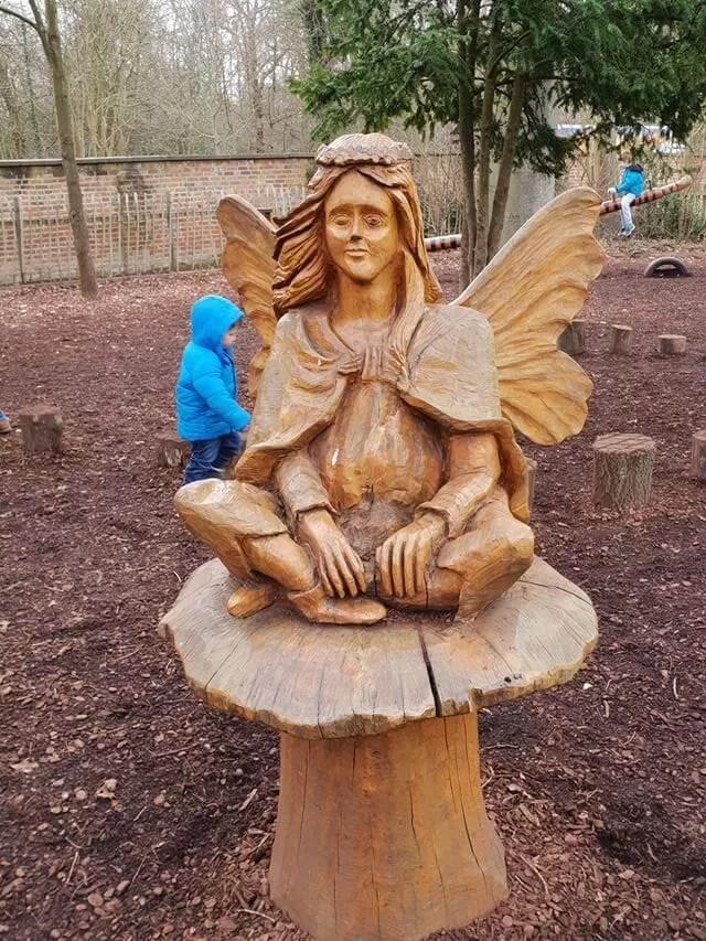 tinkerbell fairy sitting on a mushroom sculpture