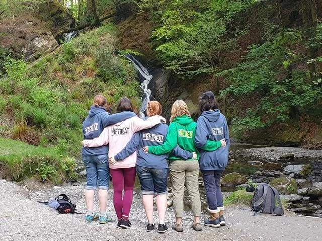 5 in retreat jumpers in front of waterfall