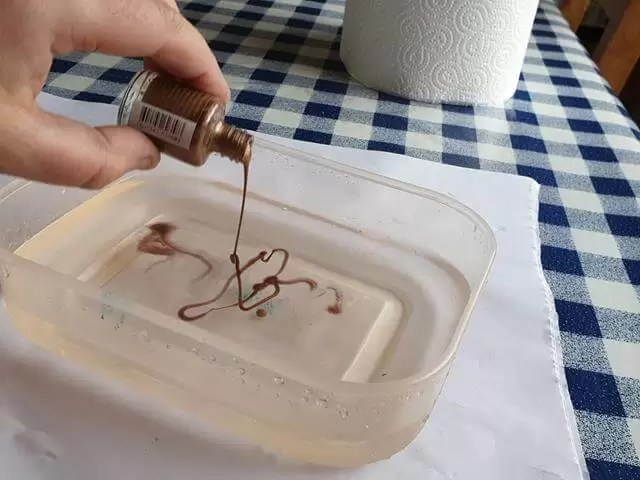pouring bronze nail polish into tub of water