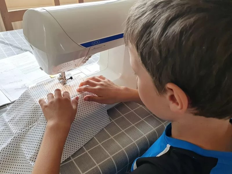 boy learning to sew with a machine