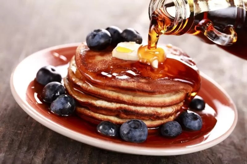 syrup on pancakes with blueberries