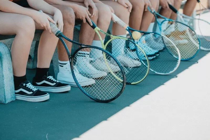 row of tennis players and rackets