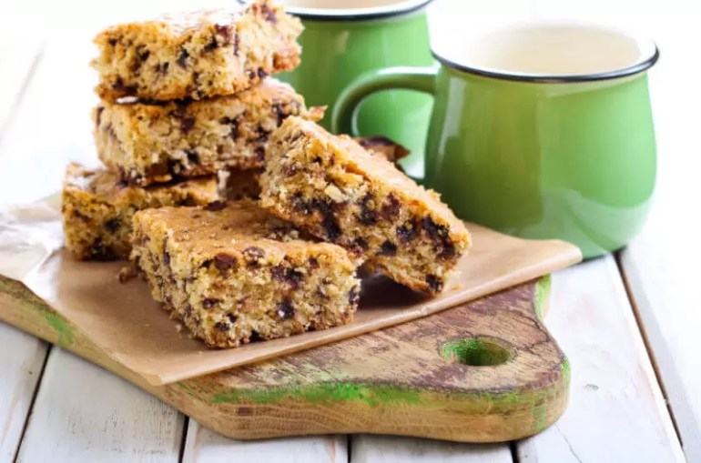 fruit flapjacks on board with green mugs behind