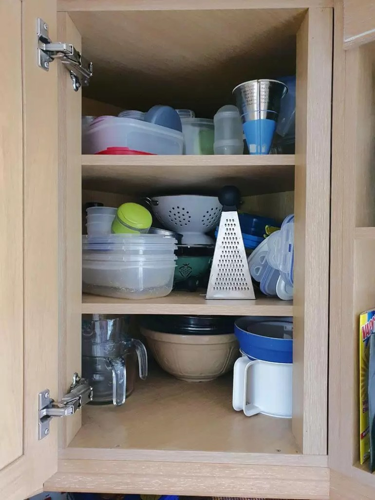tupperware and mixing bowls cupboard