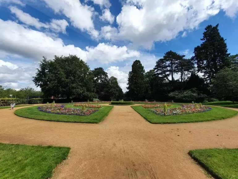 wide angle view down path through formal flower gardens
