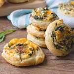Spinach and Bacon Pinwheel Sandwiches sitting on a cutting board