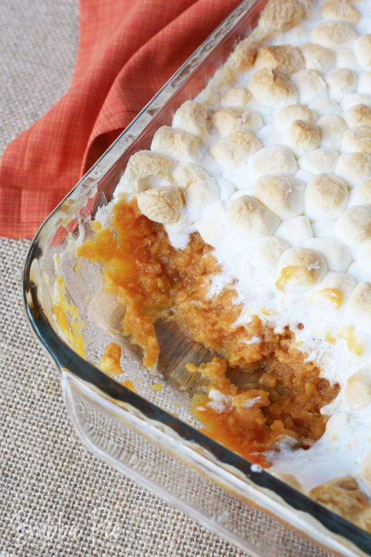 a dish of Sweet Potato casserole with marshmallows on top sitting on a counter with an orange napkin