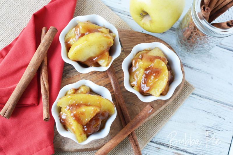 small white bowls of fried apples on a cutting board with a red napkin and cinamon sticks