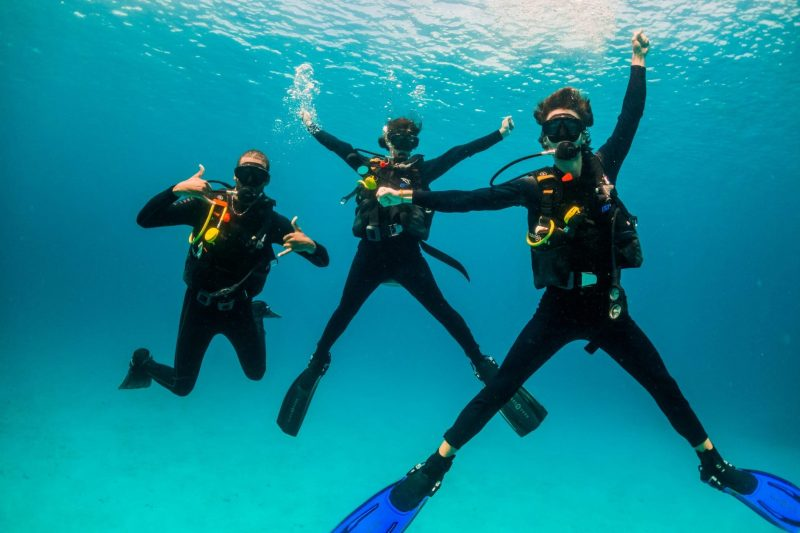 Tres buceadores bautismo de buceo