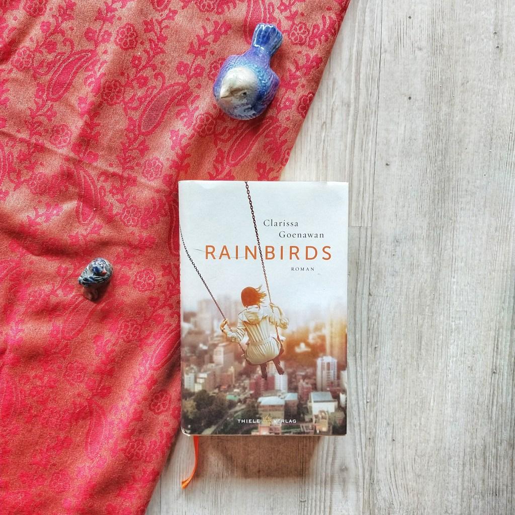 das Buch, auf dem eine schaukelnde Frau vor einer Großstadtkulisse zu sehen ist, lieg auf einem halb weiß, halb rotem Hintergrund. Um es sind Vögel aus Ton aufgestellt