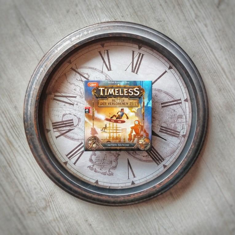 Das Bild zeigt die Hülle des Hörbuchs auf einer Uhr im Retro-Stil. Hinter dem Ziffernblatt mit römischen Ziffern sieht man eine alte Weltkarte.