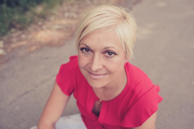 Die Autorin Nina Bilinzki, kurze, blonde Haare, schaut in die Kamera und lächelt.