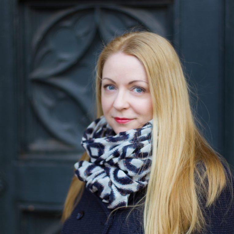 Autorin Dee Voight mit langen, blonden Haaren und einem warmen Schal lächelt in die Kamera