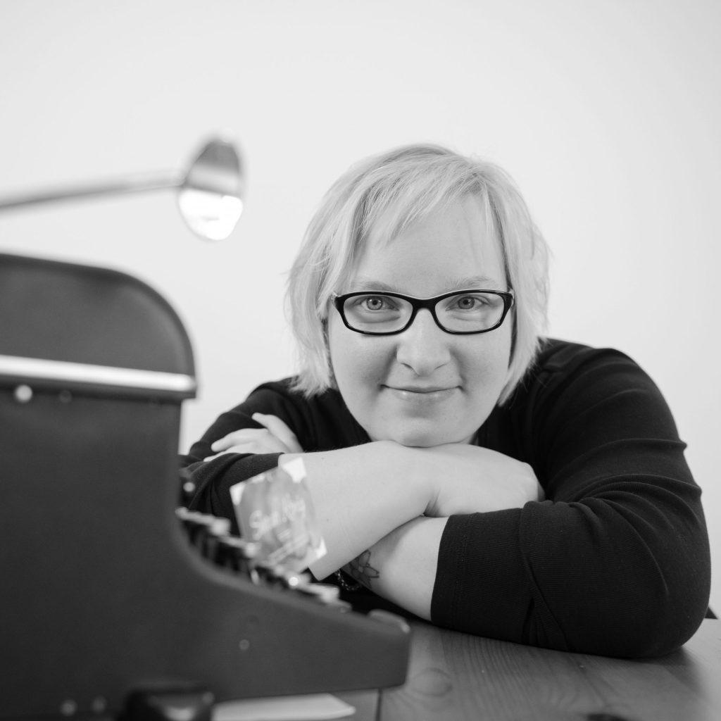 Sarah König, kurze blonde Haare, mit Brille, lächelt freundlich am Schreibtisch in die Kamera