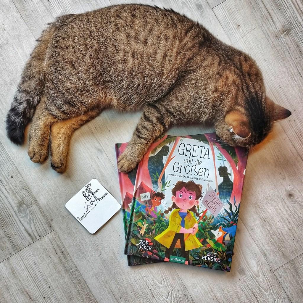 Der grau-getigerte Kater liegt über dem Buch, auf dem ein Mädchen mit zwei Zöpfen mit einem Streik-Schild inmitten des Waldes zu sehen ist. Daneben liegt ein #WirlesenFrauen Untersetzer.