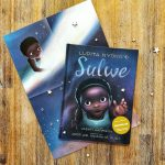 """Auf einem Holzhintergrund liegt das Buch """"Sulwe"""". Auf dem Cover ist die Illustration eines Schwarzen Mädchens zu sehen, das mit der Hand nach oben greift. Das Buch liegt auf einem halb zusammengefalteten Plakat, das Sulwe zeigt, die auf der Sternschnuppe reitet."""