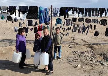 Los niños se aferran a los contenedores de agua en el campamento de al-Hol