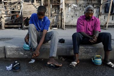 Los hombres se lavan los pies y las manos antes de las oraciones del Ramadán en la Plaza Tinubu, usando máscaras faciales y adhiriéndose a medidas de distanciamiento social para reducir la propagación del coronavirus en Lagos, Nigeria, el 13 de mayo de 2020