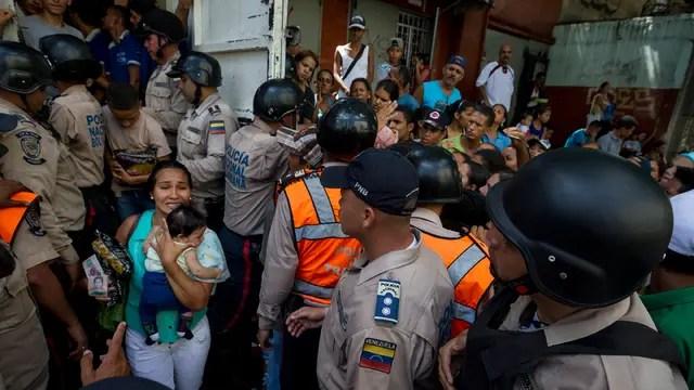 La policía contiene a personas que buscan entrar a un supermercado de Caracas