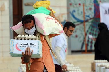 Un hombre con una máscara protectora recibe ayuda humanitaria en la tercera ciudad de Taez en Yemen, el 8 de mayo de 2020, en medio de la pandemia de coronavirus