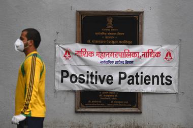 Un hombre pasa junto a un letrero que dice Pacientes positivos durante una prueba de detección de coronavirus en un centro de cuarentena, en Nashik, la India, el 13 de septiembre de 2020