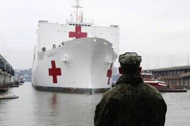 La llegada del USNS Comfort al puerto de Manhattan bajo la atenta mirada de un miembro de la Armada