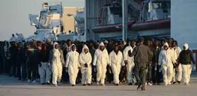 Un grupo de migrantes es custodiado por la policía italiana luego de arribar ayer a Sicilia