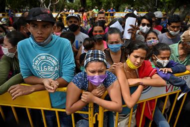 Los migrantes venezolanos que desean regresar a su país debido a la nueva pandemia de coronavirus, esperan en Cali, Colombia, la oportunidad de subir a un autobús que los llevará a la frontera, el 12 de mayo de 2020