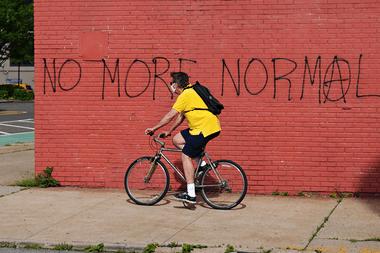 Un hombre con una máscara protectora monta una bicicleta junto a un graffiti que dice NO MÁS NORMAL durante la pandemia de coronavirus el 25 de mayo de 2020 en el distrito de Queens de la ciudad de Nueva York