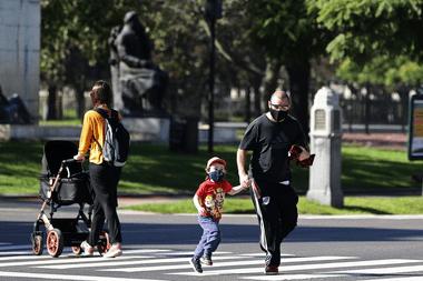La gente cruza la calle después de que las autoridades permitieron que los niños salieran durante una hora con fines recreativos, en medio del bloqueo impuesto contra la propagación del nuevo coronavirus en Buenos Aires, el 16 de mayo de 2020