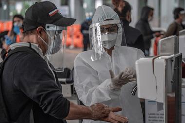 Un trabajador del Ministerio de Salud vistiendo un traje de protección contra coronavirus, le muestra a un pasajero cómo lavarse las manos correctamente en el aeropuerto internacional El Dorado de Bogotá, el 18 de mayo de 2020