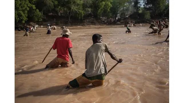 Los minero completan su trabajo de filtrado de la tierra en el río