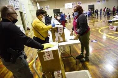 Voluntarios entregan las urnas al otro lado de la calle de la Junta Electoral del Condado de Robeson el 3 de noviembre de 2020 en Lumberton, Carolina del Norte