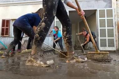 Voluntarios colaboran con la tarea de remover el barro y las montañas de desperdicios