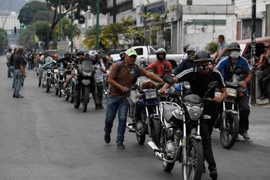 Los ciclistas empujan sus motocicletas en una fila para repostar sus tanques en una estación de servicio, en Caracas, el 25 de mayo de 2020, en medio del brote de coronavirus