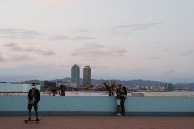 Unas pocas personas transitan por el paseo marítimo de la playa de la Barceloneta en Barcelona el 30 de mayo de 2020 mientras el país comienza a aflojar un cierre nacional para evitar la propagación del nuevo coronavirus