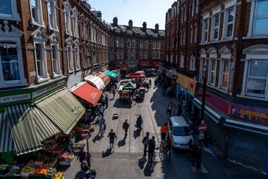 Los peatones caminan por los puestos del mercado en Electric Avenue en Brixton, sur de Londres el 23 de abril de 2020, mientras la vida en Gran Bretaña continúa bajo confinamiento para detener la propagación del coronavirus